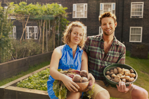 Couple with harvested potatoes and beets on council estate allotment - CUF39952