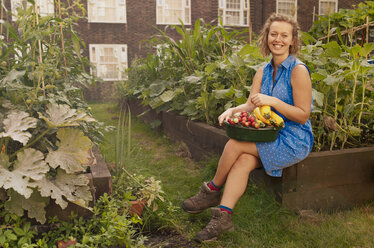 Young woman with harvested vegetables on council estate allotment - CUF39958