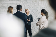 Senior businesswoman discussing with male and female coworkers in meeting at office - MASF08061