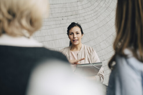Businesswoman discussing with female coworkers against wall at office - MASF08070