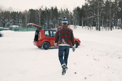 Rear view of man walking towards red car on snow covered landscape - MASF08106