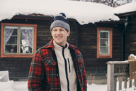 Smiling man standing against log cabin during winter - MASF08130