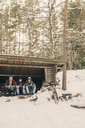 Friends sitting in log cabin against trees during winter - MASF08136