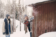 Friend looking at man throwing snowball while standing behind log cabin during winter - MASF08148