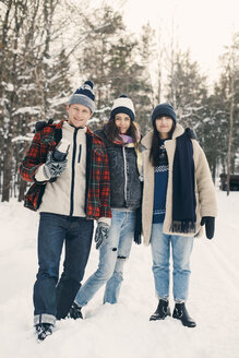 Full length portrait of smiling friends standing against trees on snow covered field - MASF08151