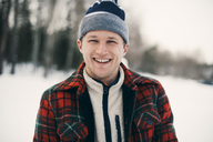 Portrait of happy man in warm clothing at park during winter - MASF08154