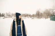 Smiling woman looking away while standing on snowy field during winter - MASF08157