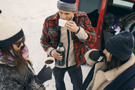 High angle view of friends having coffee while talking by car on snow - MASF08169