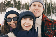 Portrait of cheerful friends wearing knit hats at park during winter - MASF08181