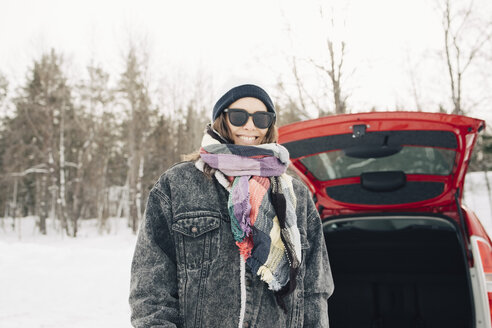 Smiling woman standing by car on snow covered landscape - MASF08190