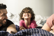 Fathers looking at cheerful daughter playing on bed at home - MASF08205