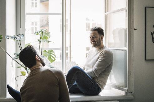 Happy gay man talking to boyfriend while sitting on windowsill at home - MASF08223