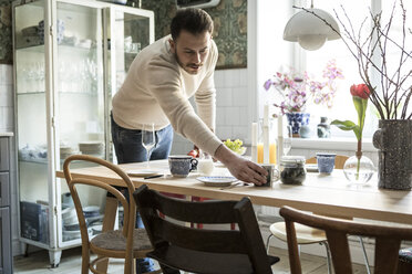Young man arranging cup on table in kitchen at home - MASF08229