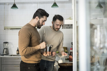 Gay couple preparing food in kitchen at home - MASF08232