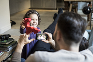 Smiling daughter showing red block to fathers resting in living room - MASF08235