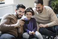Fathers and daughter looking at smart phone while sitting on sofa at home - MASF08238