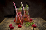 Two glass bottles of homemade raspberry lemonade flavoured with rosemary - LVF07235