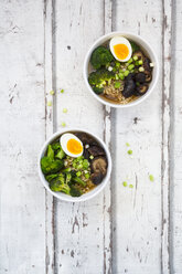 Two bowls of Ramen soup with egg, broccoli, noodles, shitake mushroom and spring onions - LVF07241