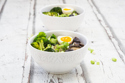 Two bowls of Ramen soup with egg, broccoli, noodles, shitake mushroom and spring onions - LVF07244