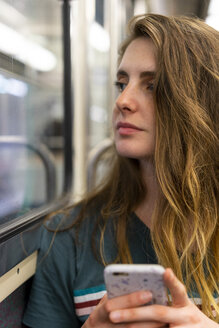 Portrait of young woman with smartphone in underground train - AFVF00741
