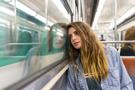 Portrait of pensive young woman in underground train - AFVF00744