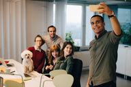 Smiling businessman taking selfie with colleagues at dog at creative office - MASF08254