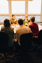 Multi-ethnic business coworkers sitting at desk while discussing in board room - MASF08272