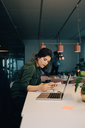 Side view of businesswoman using smart phone while working at desk in creative office - MASF08302