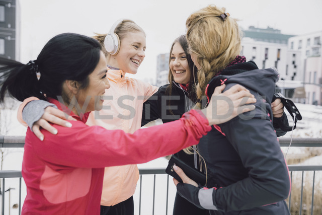 Happy friends embracing while standing on bridge in city during winter - MASF08314