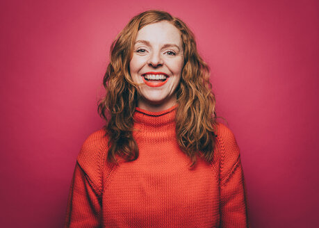 Portrait of smiling woman in orange top against pink background - MASF08335