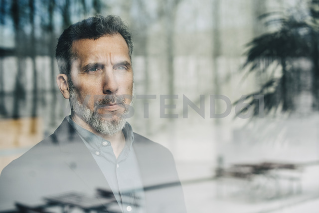 Close-up of thoughtful businessman seen through glass window at office - MASF08347