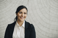 Smiling businesswoman standing against wall at office - MASF08377