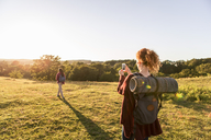Rear view of woman photographing daughter standing on field against sky during sunset - MASF08434