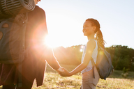 Smiling girl holding hands with mother while hiking at park against sky during sunset - MASF08440