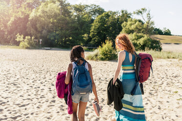 Rear view of mother and daughter with backpacks walking at beach on sunny day - MASF08452