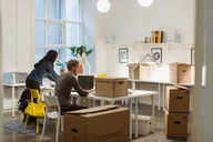 Business colleagues working at desk amidst cardboard boxes in illuminated creative office - MASF08497