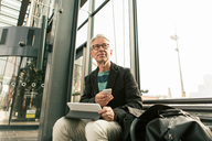 Low angle view of senior male commuter looking away sitting with technologies by bags at railroad station - MASF08530