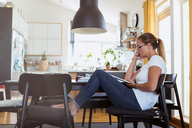 Side view of woman watching digital tablet while sitting on chair at home - MASF08548