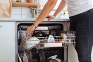 Midsection of woman using dishwasher while standing in kitchen - MASF08554