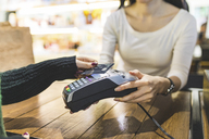 Customer paying cashless with credit card in a shop - WPEF00667