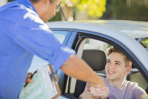 Happy learner driver and instructor shaking hands in car - ZEF15792