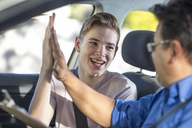 Happy learner driver and instructor giving a high five in car - ZEF15795