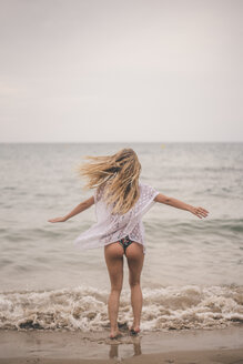 Rear view of young woman standing with outstretched arms on the beach - ACPF00100
