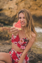 Portrait of happy young woman on rocks at the sea holding watermelon slice - ACPF00103