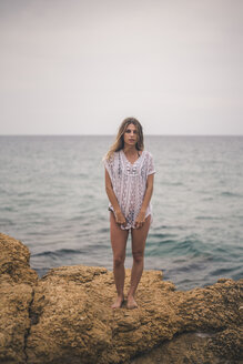 Portrait of young woman standing on a rock at the coast - ACPF00109