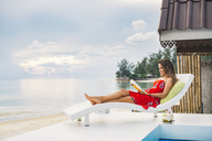 Thailand, Koh Phangan, woman reading book on the beach - MOMF00470