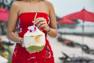 Thailand, woman holding fresh coconut, partial view - MOMF00479