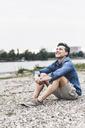 Smiling man sitting at the riverside looking up - UUF14460