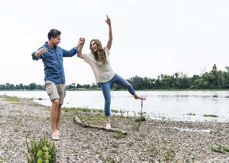 Playful couple at the riverside - UUF14475