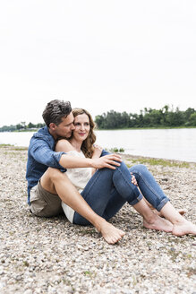 Affectionate couple sitting at the riverside - UUF14487